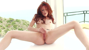 Red-haired babe toys cunny with dildo by the window