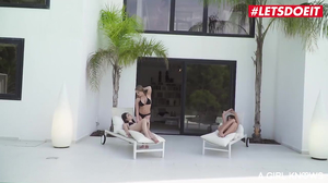 Hot lesbian threesome close to an outdoor pool